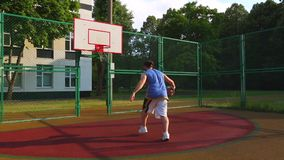 Motivaci?n del deporte Baloncesto de la calle El jugador anota la bola en la cesta en la corte de la calle Juego de entrenamiento almacen de metraje de vídeo