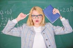 Motivaci?n inspiradora de la chispa del educador Fondo del libro del control de la mujer del educador y de la pizarra de la pluma imagen de archivo libre de regalías
