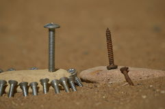 Motivate and retain. Photo of two groups of bolts, a first group of screws are light-colored and also look new, while on the other stone two screws are rusted Royalty Free Stock Photos
