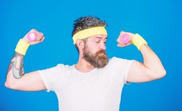 Motivated athlete guy. Sportsman training with dumbbells blue background. Improve your muscles. Man bearded athlete stock photo