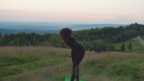 Pretty sporty fitness african american female working out revolved triangle yoga pose in nature at dawn