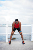 Motivated black male runner resting. Male runner resting. Black man taking a running workout break for breathing. Sport motivation concept Stock Image