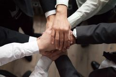 Motivated business people put hands together, trust and support. Motivated business people put hands together, sales team engaging in teambuilding activity royalty free stock photo