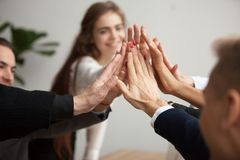 Motivated business team giving high five, close up of hands. Motivated successful business team giving high five, happy young students employees group join hands Stock Photos