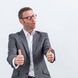 Motivated businessman with thumbs up expressing support Royalty Free Stock Image