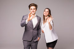 Motivated businessman and woman giving a okay gesture of approval and success as they pose side by side giving the camera big frie Stock Photography