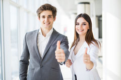 Motivated businessman and woman giving a thumbs up gesture of approval and success as they pose side by side giving the camera big stock image