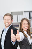Motivated businessman and woman giving a thumbs up Royalty Free Stock Photography