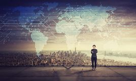 Motivated businesswoman on the rooftop of skyscraper. Sunset time and world map hologram projection on the sky. Modern technology stock photo