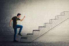 Motivated and confident young man hurry to climb a imaginative staircase stock images