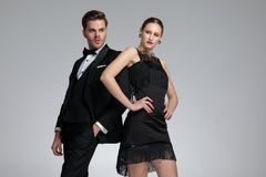 Motivated couple posing leaning on each other. And looking sideways while he is holding his hand in his pocket and she is standing with her arms on her hips on royalty free stock photos