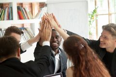Motivated excited multiracial business team giving high five at. Motivated excited multiracial business team giving high five celebrating corporate growth and Royalty Free Stock Photos
