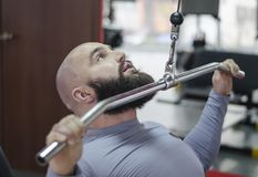 Motivated fit sportsman working hard at fitness club, doing pulldown exercises. Stock footage Stock Photography