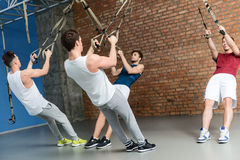Motivated four sportsmen training body with equipment. Muscular confident young men doing push-ups in gym. They are hanging on trx straps Royalty Free Stock Images