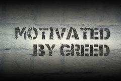 Motivated by greed gr. Motivated by greed stencil print on the grunge white brick wall royalty free stock image