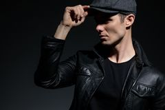 Motivated guy arranging his cap and looking to the side. Motivated tough guy arranging his cap and looking to the side while wearing a black t-shirt and leather royalty free stock photos