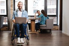 Motivated handicapped man writing his research paper stock photography