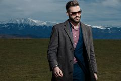 Motivated man curiously looking and walking to the side. While wearing sunglasses, gray coat and blue suit on outdoor background royalty free stock photos