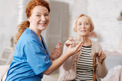 Motivated optimistic nurse happy helping her patient Royalty Free Stock Photos