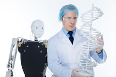 Motivated precise man holding a 3D model of the genome Royalty Free Stock Images