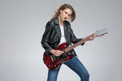 Motivated punk girl playing electric guitar. And wearing a black leather jacket while standing on gray studio background stock images