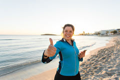 Motivated sporty woman doing thumbs up success gesture after urban workout on seashore. Royalty Free Stock Images