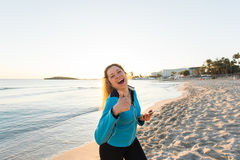 Motivated sporty woman doing thumbs up success gesture after urban workout on seashore. Stock Image
