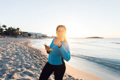 Motivated sporty woman doing thumbs up success gesture after urban workout on seashore. Royalty Free Stock Photography
