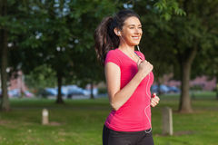 Motivated sporty woman running in a park Royalty Free Stock Photos