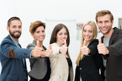 Motivated successful business team. Of diverse young professionals giving a thumbs up to show their agreement and support or to indicate a victory Royalty Free Stock Image