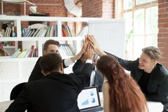 Motivated team of coworkers giving each other high fives. Motivated team of coworkers giving each other high fives, celebrating corporate growth. Pie chart and Stock Image