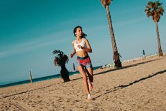Motivated to shape her body. Full length of beautiful young woman in sports clothing jogging while exercising outdoors stock photos