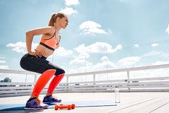 Motivated woman is doing squats on sunny terrace stock images