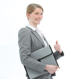 Motivated woman giving a thumbs up. Motivated smiling professional woman in a fashionable jacket carrying a folio file giving a thumbs up Stock Image