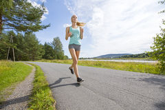 Motivated woman runs fast on a road in the forest Royalty Free Stock Photography