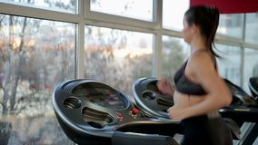 Motivated woman training in the gym, running on treadmill, active lifestyle. Stock footage stock video