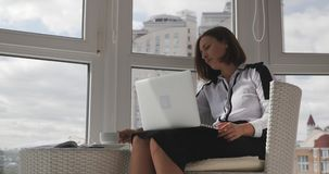 Motivated young beautiful brunette business woman sitting in modern white chair, drinking coffee and looking at big city through o. Ffice windows stock video footage