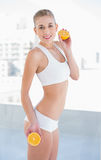 Motivated young blonde model holding two halves of an orange. Motivated young blonde model in white sportswear holding two halves of an orange stock photo