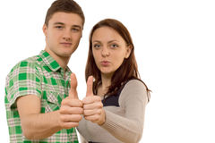 Motivated young couple giving a thumbs up Stock Image
