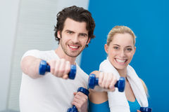 Motivated young couple working out with dumbbells. Motivated attractive young couple working out with dumbbells standing side by side giving the camera a Stock Photography