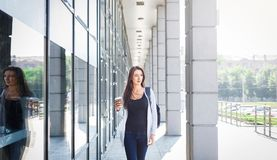 Motivated young female IT student, drinking coffee before lesson. Motivated young brunette female student with backpack on the way to university. Drinking coffee royalty free stock image