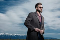 Motivated young man closing his gray coat`s buttons. And looking to the side hopeful while wearing a blue suit and sunglasses, standing on outdoor background royalty free stock images