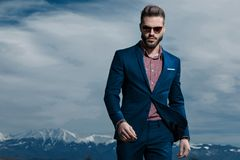 Motivated young man walking forward while wearing sunglasses. A checkered shirt and blue suit on outdoor background stock photos