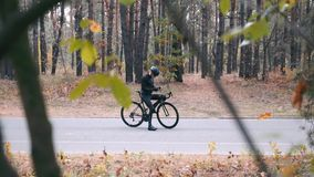 Motivated young professional cyclist in black helmet is typing message, putting phone in his pocket and starting to ride on road b. Ike in fall park. Autumn stock video