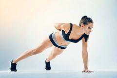 Motivated young woman doing one arm pushup. Beneficial activity. Confident fitness lady in a navy blue sportswear doing a one arm push up with one hand on the Stock Image