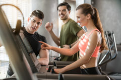Young woman increasing the speed during a workout session superv. Motivated young women increasing the speed of the treadmill during a workout session supervised Stock Image
