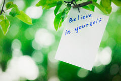 Motivating phrase Believe in yourself. On a green background on a branch is a white paper with a motivating phrase. Royalty Free Stock Images