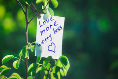 Motivating phrase love more worry less. On a green background on a branch is a white paper with a motivating phrase. Stock Image