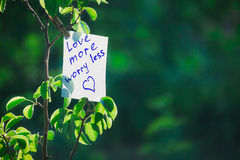 Motivating phrase love more worry less. On a green background on a branch is a white paper with a motivating phrase Royalty Free Stock Photo