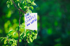 Motivating phrase You can change the world. On a green background on a branch is a white paper with a motivating phrase.  Stock Photography